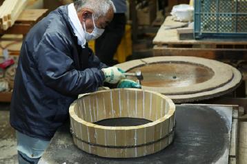 職人が素材を生かした組み方で、色合わせ、目合わせをしながら一つ一つ組み立てます。この、桶の原形をつくる作業を「丸め」と呼んでいます。手作業で丁寧に組んでいくため、狂いがでにくいおひつに仕上がります。ぴったりと隙間なく組んでいくのは長年培ってきた職人技によるもの。できるだけ凸凹をなくして作る必要があるため、金槌片手の作業でかなりの重労働となります。