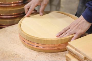 職人が素材を生かした組み方で、色合わせ、桶の直径に合わせて底板をしっかりはめ込みます。この底板の大きさがポイントです。大きすぎるとタガが切れてしまい、小さすぎると底板がはずれてしまします。とても微妙なのですが、一つ一つ大きさがちがうので、切った底板を各々の桶に合わせてからはめ込みます。